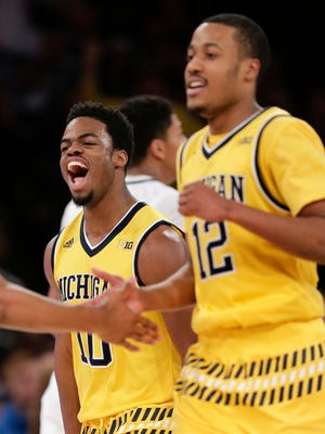 Derrick Walton Jr. gives out a yell as he heads back to the bench with Muhammad-Ali Abdur-Rahkman during a timeout.