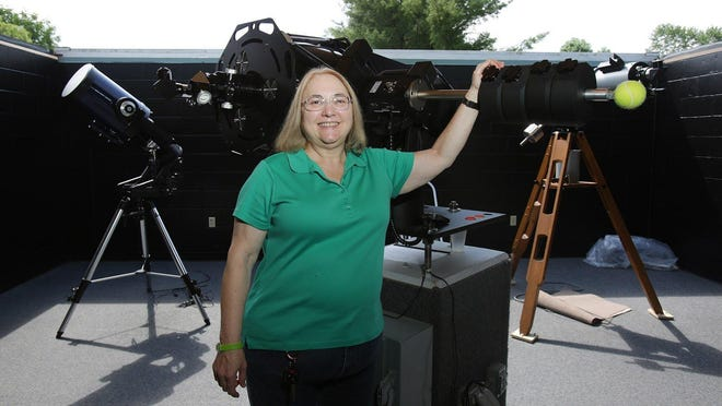 Robin Gill, astronomy education specialist at The Wilderness Center, poses with some of the center's telescopes in the Astronomy Education Building.