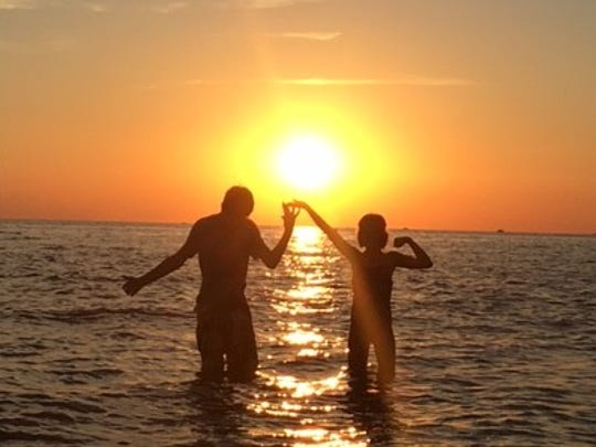 Dominic Geskey and his sister Claire Geskey try to hold up the sun to make the day last longer during a family vacation at Ludington State Park.