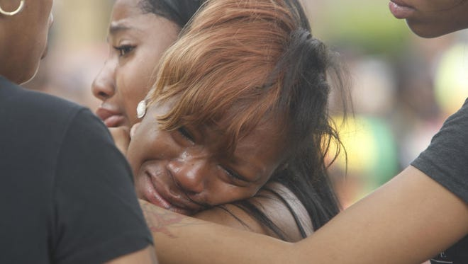 Amari Hall cries while holding onto Finesse Dillard at a prayer session on Aug. 20, 2015, following the Genesee Street shootings.