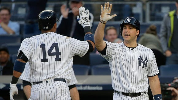 New York Yankees' Starlin Castro (14) is greeted by Mark Teixeira after hitting a solo home run against the Kansas City Royals during the first inning of a baseball game Thursday, May 12, 2016, in, New York. (AP Photo/Julie Jacobson)