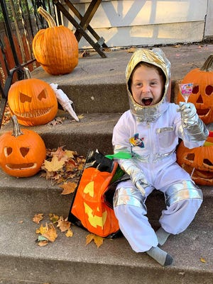 Hayes Jacobs shows he is ready to help other children have a fun Halloween as he sits on the porch on Thursday at his home in Freeport.