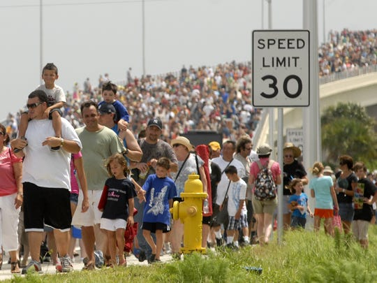 Thousands pour over the A. Max Brewer Bridge in Titusville after the final launch of the space shuttle Atlantis on July 8, 2011.