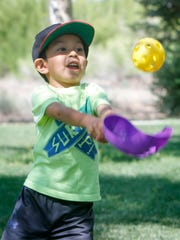 Easton Riggs plays catch with his mother Rachel Riggs Tuesday during a Park Play Day presented by the city of Farmington Parks, Recreation and Cultural Affairs department at Westland Park in Farmington.