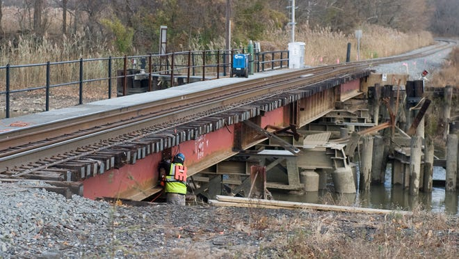 A worker works at the site where a freight train derailed on a railroad bridge over the Mantua Creek in Paulsboro last year. 11.25.13