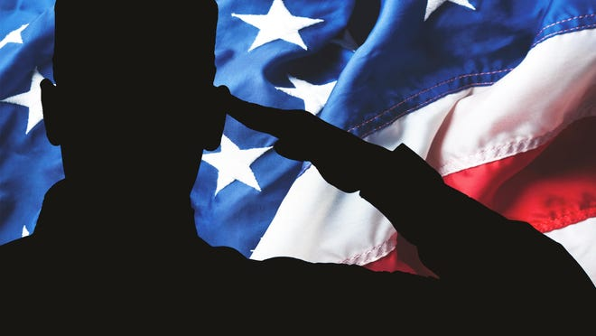 A soldier salutes the American flag.