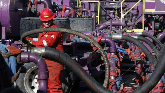 An oil-services worker adjusted hoses pumping  fluids during hydraulic fracturing March 25, 2014, at an Encana Corp. well near Mead, Colo.