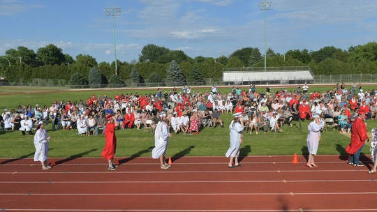 Boone High School seniors make a line to get their diploma during the school's 2020 graduation ceremony at Goeppinger Field on Saturday in Boone. Photo by Nirmalendu Majumdar/Ames Tribune
