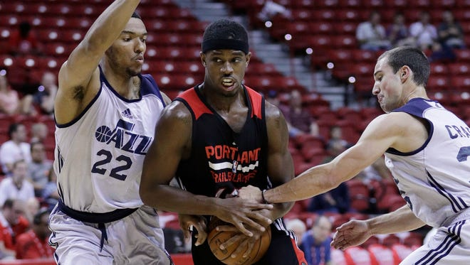Portland Trail Blazers' CJ Fair, center, drives between Utah Jazz's Joel Bolomboy, left, and Aaron Craft during the first half of an NBA summer league basketball game Wednesday, July 13, 2016, in Las Vegas.