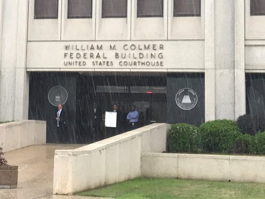 Several people wait for the rain to let up at William M. Colmer Federal Courthouse.