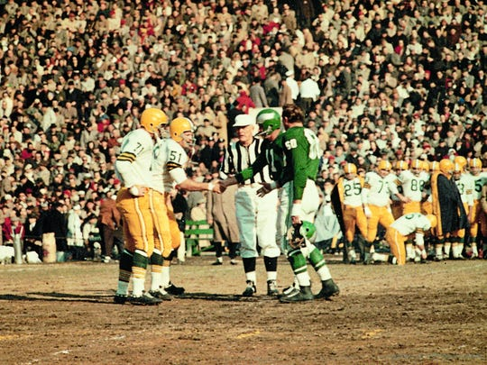 Philadelphia Eagles quaterback Norm Van Brocklin and lineman Chuck Bednarik shake hands at the coin toss to start the 1960 NFL title game the Eagles won  championship game before they defeated  the reen Bay Packers 17-13  at Franklin Field