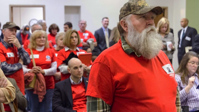 David Jones of Lawrenceburg, Tenn., and other opponents of Gov. Bill Haslam's Insure Tennessee proposal watch a committee hearing on a television in the legislative office complex in Nashville on Feb. 3, 2015.
