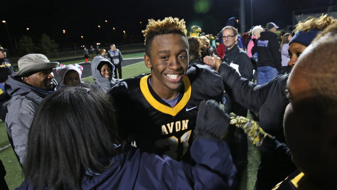 Avon High School's No. 31 Bryant Fitzgerald is all smiles as he gets hugs and congratulations from family and friends Oct. 30, 2015, after his team won the sectional over Ben Davis 27-22.