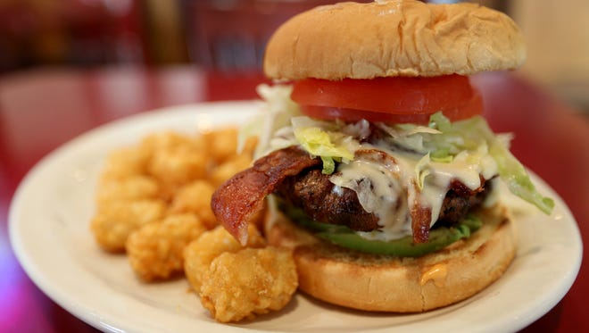 The Southern Route Burger topped with avocado, bacon pepper jack cheese and chipotle mayo is served with tater tots at Cafe 22 between Salem and Dallas on Highway 22.
