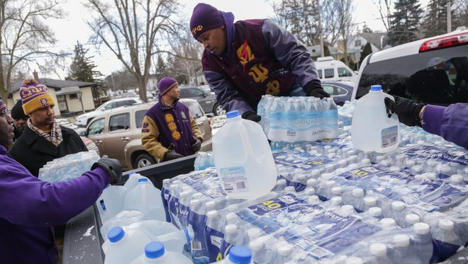 Kammal Smith of Troy of Omega Psi Phi Fraternity Inc. helps move waters to hand to other members that they donated to the Flint community at Heavenly Host Baptist Church in Flint on Sunday January 17, 2016. The fraternity members from throughout the state brought in five truckloads of water for Flint residents to deliver to church members and then to the community.