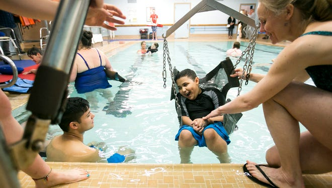 Leonardo Garibay smiles as he is lowered into the water for a swimming session at the YMCA on Wednesday, April 27, 2016. The weekly outing gives Garibay and other Salem-Keizer students with cerebral palsy, muscular dystrophy and other mobility limitations a chance to exercise and enjoy the water.