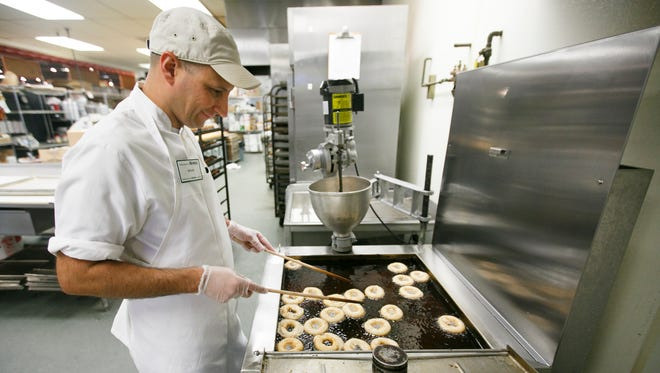 Brian Sanchez, a bakery manager at Roth's, flips over doughnuts in the fryer on Monday, May 23, 2016. The bakery makes about 700 doughnuts a day, although Sanchez says that number goes up dramatically in the holiday season and on occasions like National Doughnut Day on June 3.