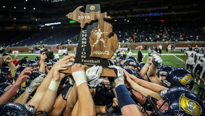 Pewamo-Westphalia's players celebrate winning the Division 7 high school title against Detroit Loyola on Saturday Nov. 26, 2016, at Ford Field in Detroit.