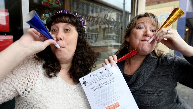 Amy Schroeder, left, and Cyndi Leinassar, with Community Action Agency, invite people the ring in the new year by donating to the Non New Year's Event Fundraiser for Feeding the Children.