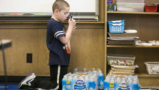 Fourth grader Tyson Turner writes his name on a water bottle at Valley Inquiry Charter School in Salem on March 16.
