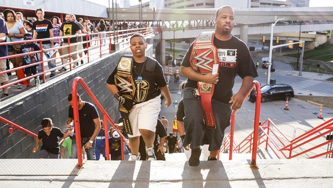 Wrestling fans Jerimiah Tarter, 13, center left, and his father Curtis Thompson, both of Detroit, walk up stairs to enter Joe Louis Arena to attend the WWE SummerSlam, Saturday, July 29, 2017, in Detroit.