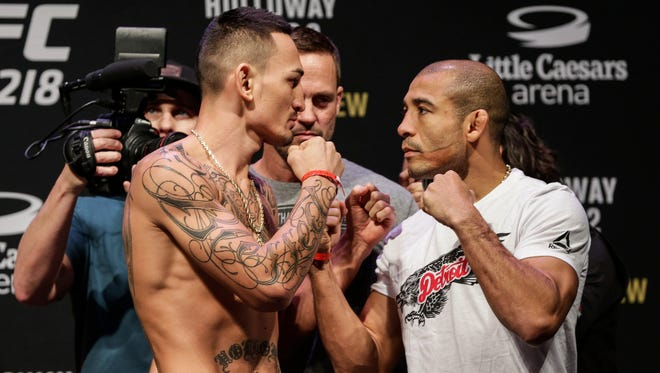 Max Holloway, left, and Jose Aldo pose for a photo during the UFC 218 official weigh-in for Saturday's featherweight championship fight at Little Caesars Arena in Detroit, Friday, Dec. 1, 2017.