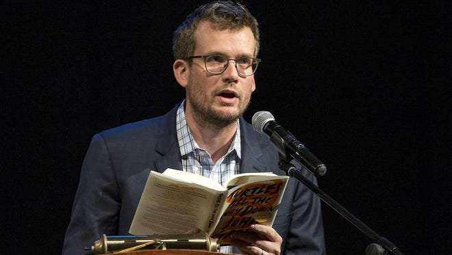 "Author John Green reads an excerpt from ""Turtles All the Way Down,"" during his appearance at the Pike Performing Arts Center, Indianapolis, Thursday, Oct. 19, 2017. Green read an excerpt from the book and answered audience questions before his brother Hank Green joined the stage to entertain."