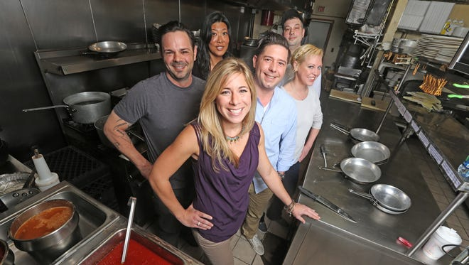 In this April 14, 2014 photo, local contestants from the Fox reality show Hell's Kitchen meet for a discussion to discuss their experiences on the show at Tony's Touch of Italy restaurant.  Anton Testino, Dana Cohen (in front), Ji Cha, Justin Antiorio, Will Lustberg and Jessica Vogel in the kitchen of Tony's.