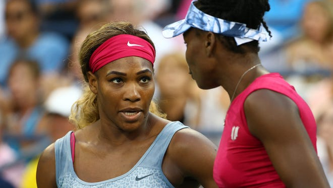 Serena and Venus Williams of the United States play their women's doubles match against Timea Babos of Hungary Kristina Mladenovic of France on day four of the 2014 U.S. Open at the USTA Billie Jean King National Tennis Center on August 28, 2014 in the Flushing neighborhood of the Queens borough of New York City.
