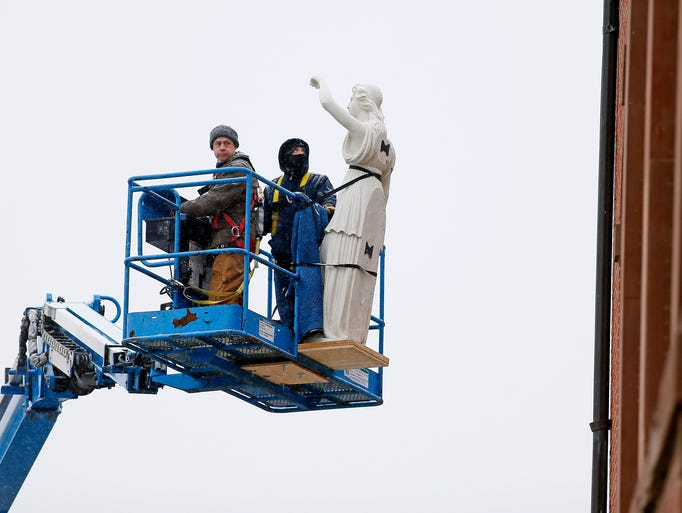 Lady Justice goes up in a lift towards the courthouse.