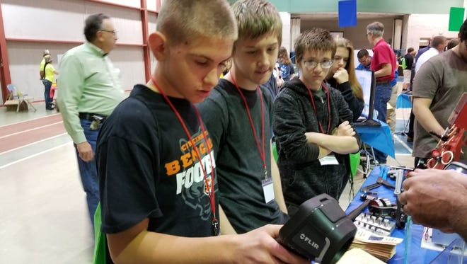 Dominic Griggs, 14, of Bellevue High School uses a thermo scan at the Whirlpool Corp. table at the THINK Manufacturing Showcase at Terra State Community College. The scan is used for electrical wiring at the plant.