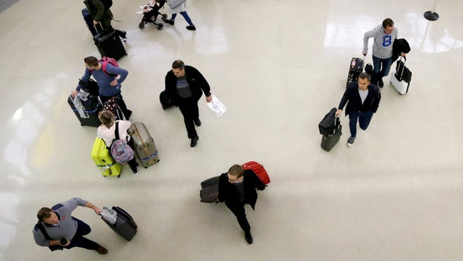 Passengers walk with their luggage as they exit customs and immigration at the international arrivals terminal at Newark Liberty International Airport, Thursday, Oct. 26, 2017, in Newark, N.J.