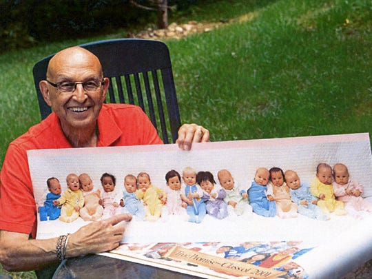 """Photographer Sam Campanaro with a print of his iconic """"15 babies"""" Colorama photo."""