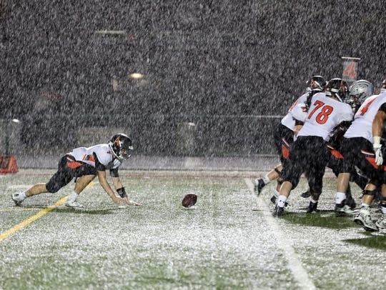 Ames High senior quarterback Joe Evans (7) drops the