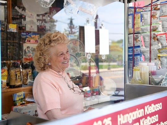 Dolores Santucci sells hot dogs and sausages from the cart outside of Karl Ehmer Meats deli, which is owned by her son, on Broadway in Hillsdale.