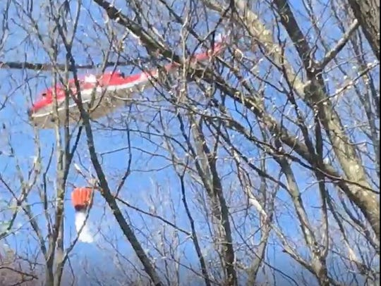A New Jersey Forest Fire Service Helicopter drops water