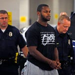 Phoenix police officers escort Arizona Cardinals running back Jonathan Dwyer, 25, to the 4th Avenue Jail in Phoenix, following his arrest on suspicion of aggravated assault.