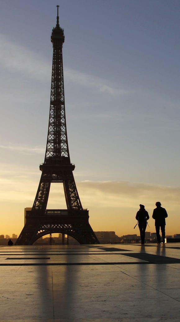 People walk at sunrise on the Trocadero Esplanade in