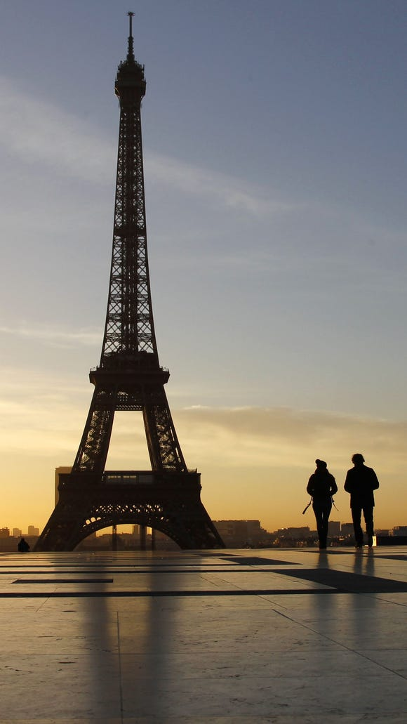 People walk at sunrise on the Trocadero Esplanade in front of the Eiffel Tower in Paris in February 2014.