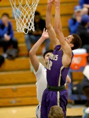 North Kitsap's Kainen Warren puts back an offensive rebound in for a basket against Olympic Tuesday night at Olympic. Behind him is Olympic's Jaiden Mosley.