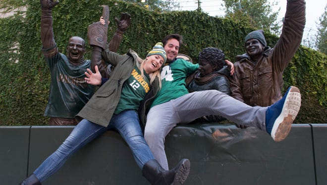 Merel and Jordi Baggen pose with the Lambeau Leap statue before the Green Bay Packers game against the Chicago Bears. The couple left their four children at home in Netherlands to attend the game.