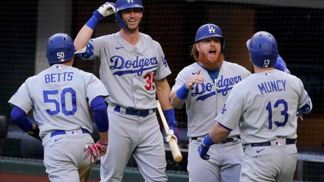 Los Angeles Dodgers' Max Muncy (13) celebrates his grand slam home run during the first inning in Game 3 of a baseball National League Championship Series against the Atlanta Braves Wednesday, Oct. 14, 2020, in Arlington, Texas.