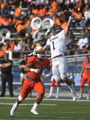 Nevada's McLane Mannix (1) attempts to make a catch while taking on Idaho State and Paea Moala (51) during their football game at Mackay Stadium.