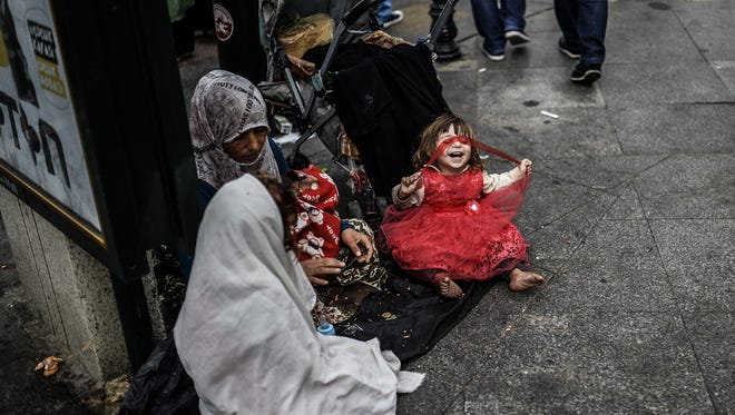 A Syrian woman with her four children begs on September 17, 2014 in the street in Istanbul. Turkey is currently hosting more than 1.5 million Syrian refugees.