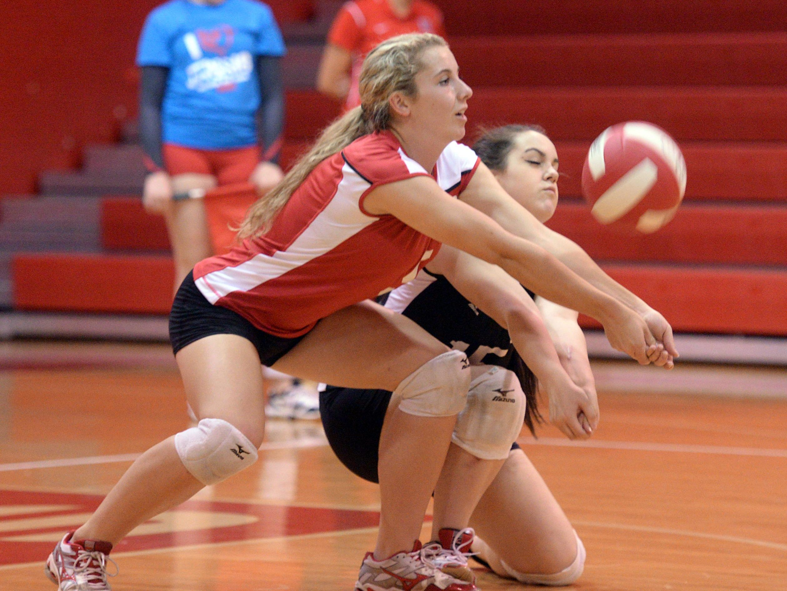 Ruston's Kara Goff gets tied up with teammate Reanne Ginn as they return volley against Haughton in volleyball.