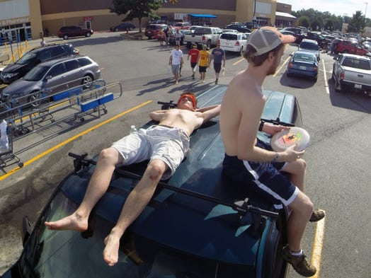 Zack Ferguson and Robert Lewis wait in the Wal-Mart parking lot in Manchester, Tenn., for the Bonnaroo gates to open on Wednesday, June 11, 2014.