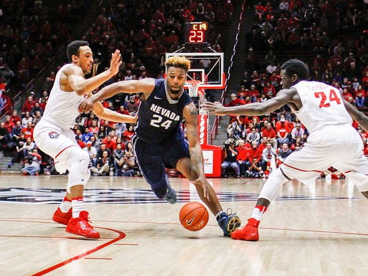 Nevada's Jordan Caroline (24) splits New Mexico's defense of Elijah Brown, left, and Damien Jefferson (24) during the second half of an NCAA college basketball game in Albuquerque, N.M., Saturday, Jan. 7, 2017. Nevada won in overtime 105-104. (AP Photo/Juan Antonio Labreche)