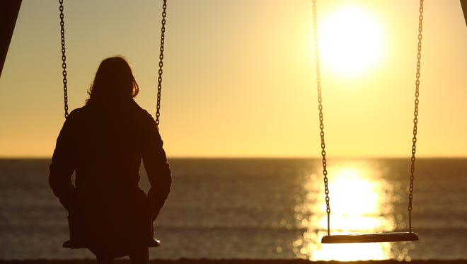 Lonely woman watching sunset alone in winter on the beach at sunset.