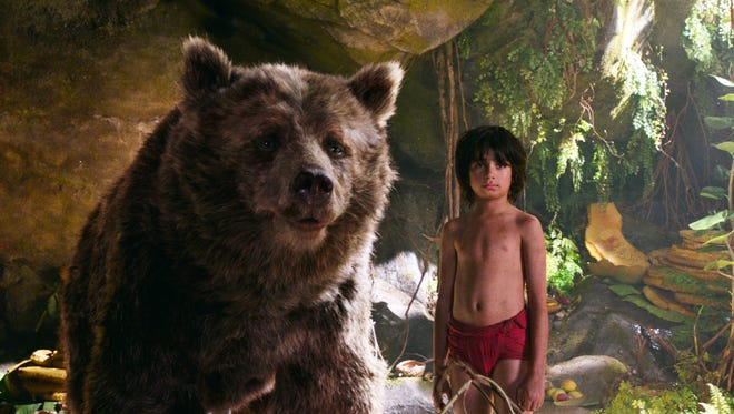 """Mowgli, portrayed by Neel Sethi, right, and Baloo the bear, voiced by Bill Murray, appear in a scene from """"The Jungle Book."""""""