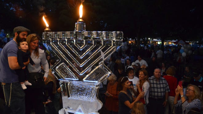 Families take menorah selfies in 2014 at Chabad of Naples' Celebration of Frozen Hanukkah, with an ice sculpture menorah, in Cambier Park. This year the event will feature a giant chocolate menorah.